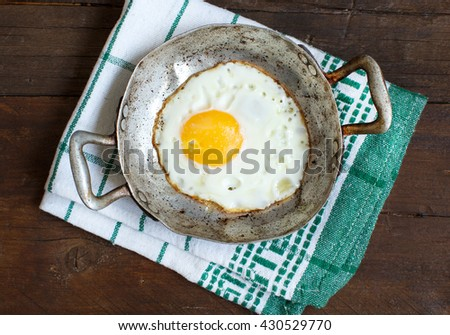 Fried egg in a old frying pan on napkin and wood