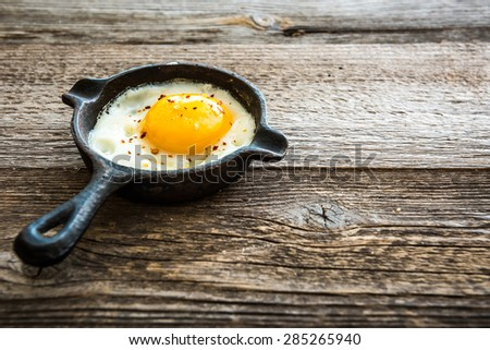 fried egg in a pan on wooden background, breakfast - stock photo