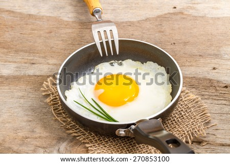 fried egg in a pan with a fork   - stock photo