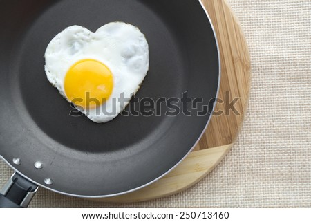 Fried egg in a shape of the heart on the pan. Cutting board and weave cloth under. - stock photo