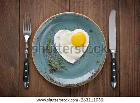 Fried egg in shape of heart on blue plate top view - stock photo
