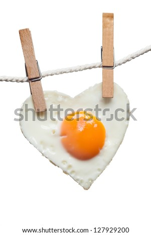 Fried egg in shape of love heart hung from wooden clothes pins or pegs, white background.
