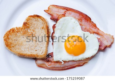 Fried egg in the shape of a heart with bacon and toast.