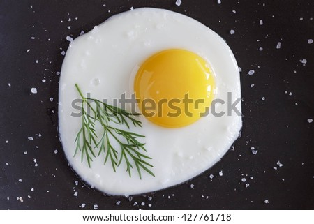 Fried egg on a black background, or in a pan. Flat position, top view. - stock photo