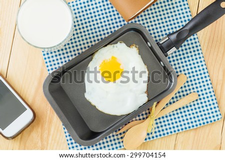 Fried egg on a pan and served with milk - stock photo
