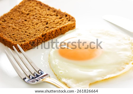 Fried egg on a plate with flatware - stock photo