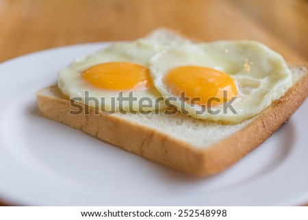 Fried egg on a slice of bread in the morning. - stock photo