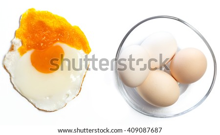 Fried egg on a white background next to a glass bowl with a few healthy unbreakable eggs, concept of being different