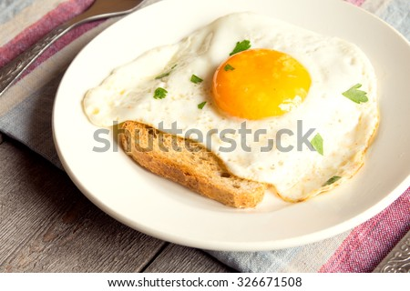 Fried egg on bread for breakfast on plate and rustic table - stock photo