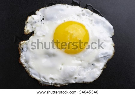 Fried egg over black textured plate background