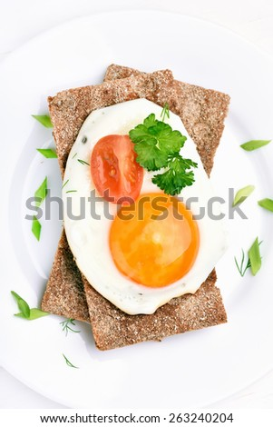 Fried egg, parsley and tomato slice on crispbread, top view - stock photo
