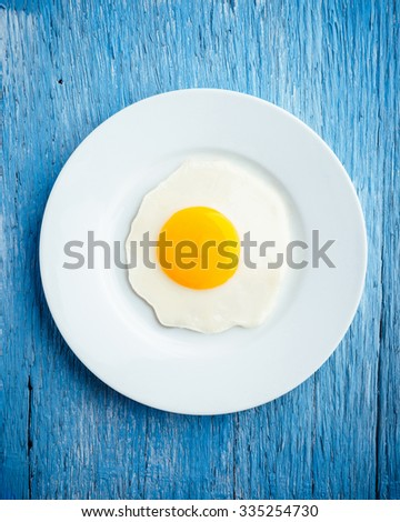 Fried egg.  Top view of white dish with fried egg on wooden background. - stock photo