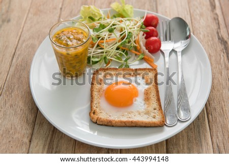 Fried egg, vegetable salad and passion fruit juice on wood table