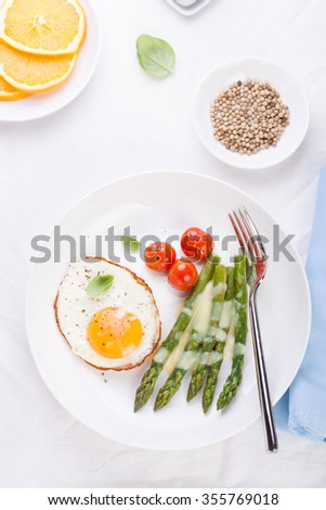 Fried egg with asparagus and tomatoes on a white plate. Top view - stock photo