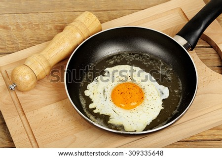 fried egg with pepper in frying pan  - stock photo