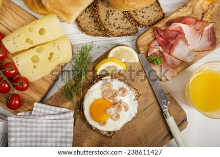 Fried egg with shrimps on protein bread, cheese, ham, juice