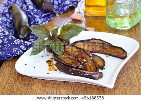 Fried eggplant with ginger and soy sauce on a white plate - stock photo
