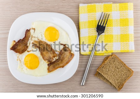 Fried eggs and bacon in glass plate, fork on napkin and bread on wooden table, top view - stock photo