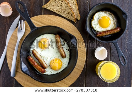 Fried eggs and sausage links in cast iron skillet sitting on kitchen table with whole wheat toast and orange juice - stock photo