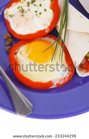 fried eggs and tortilla with salad served on blue plate with cutlery isolated over white background - stock photo