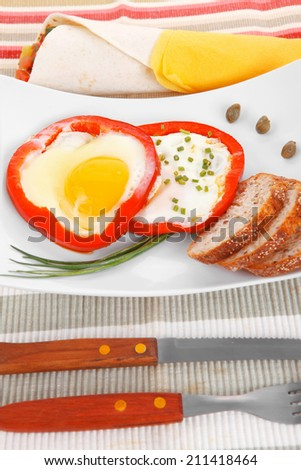 fried eggs and tortilla with salad served on white plate with cutlery over tablecloth in restaurant - stock photo