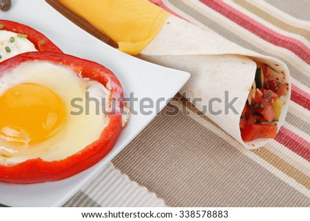 fried eggs and tortilla with salad served on white plate with cutlery over tablecloth in restaurant