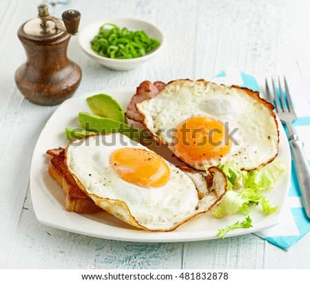 fried eggs, bread and bacon on white plate