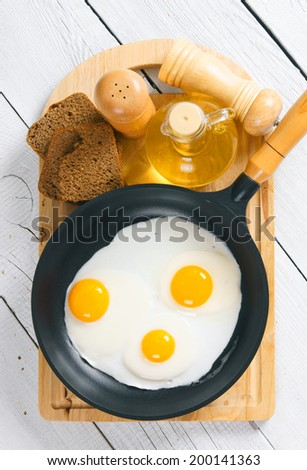 Fried eggs in a frying pan, an olive oil, rye bread, a saltcellar on a chopping board. On a wooden background.