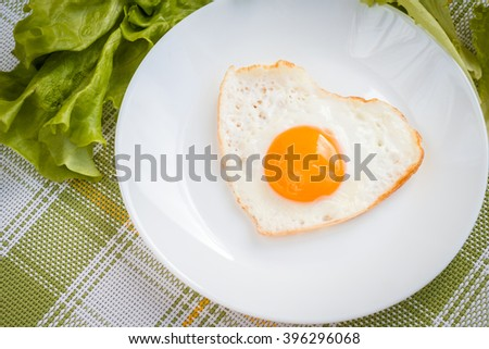 Fried eggs in form of heart. Healthy breakfast of fresh vegetables and eggs. - stock photo