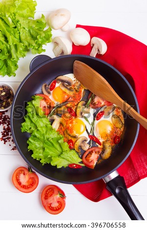 Fried eggs in pan with salad, tomato, pepper and spice on wooden background