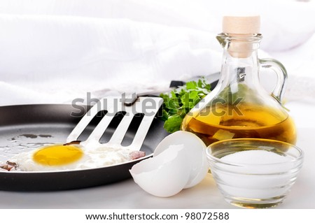 Fried eggs on a frying pan with olive oil and an egg shell - stock photo
