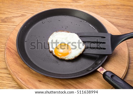 fried eggs on a pan. Pan stands on a wooden table. view from above