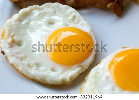 fried eggs on a white plate - stock photo