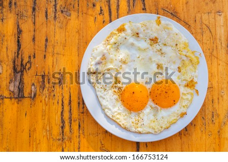 Fried eggs on wooden background  - stock photo