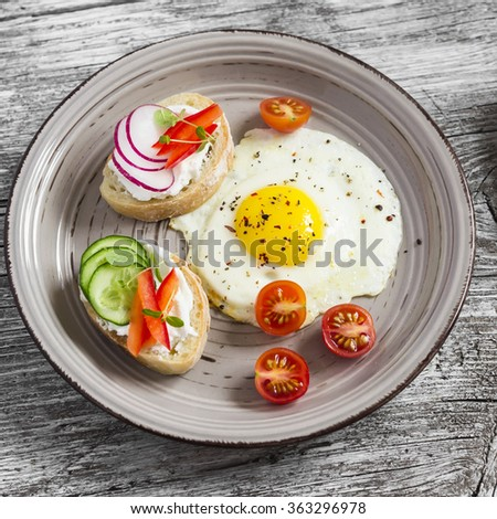 Fried eggs, tomatoes and sandwiches with cucumber, radish and soft cheese. On a light wooden table. Rustic style. Healthy breakfast or snack - stock photo