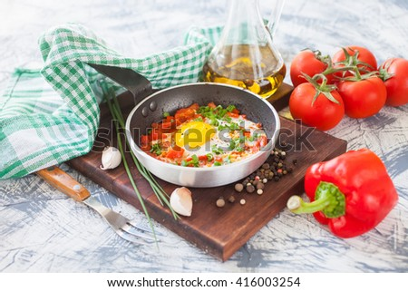 fried eggs with a tomato and a paprika in a frying pan on a board, selective focus - stock photo