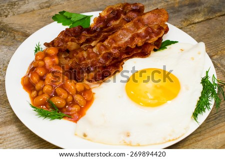 fried eggs with bacon and beans - stock photo