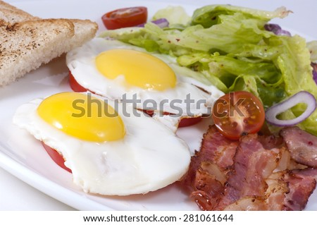 fried eggs with bacon and lettuce closeup on a white plate.