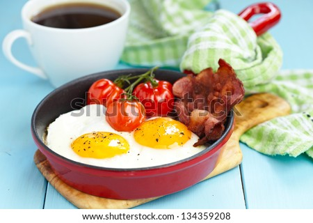 Fried eggs with bacon and tomatoes - stock photo
