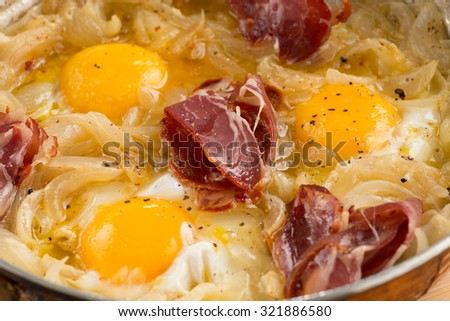 fried eggs with bacon in a pan close-up. top view  - stock photo