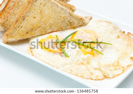 fried eggs with buttered toast and chives