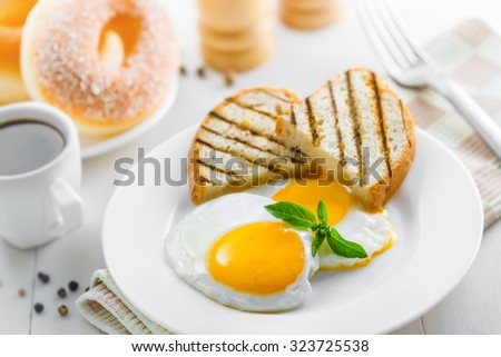 Fried eggs with coffee and dessert on breakfast. International cuisine. - stock photo