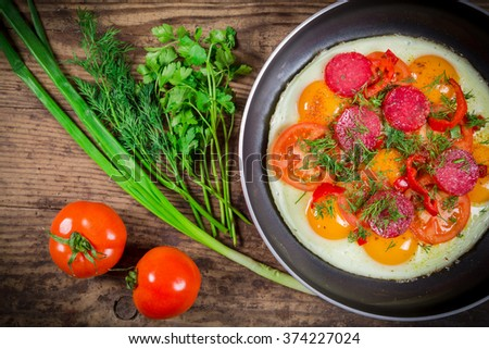 Fried eggs with greens, sausage and tomato slices on pan, wooden background