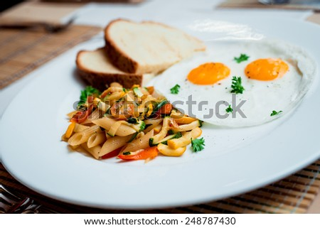 Fried eggs with pasta on the white plate. Restaurant - stock photo