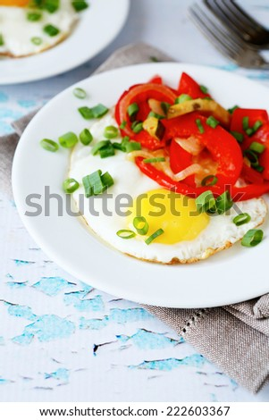 Fried eggs with peppers and onions in a bowl, delicious food