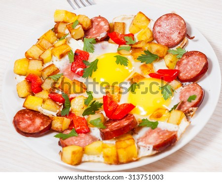 fried eggs with potato, sausage and pepper
