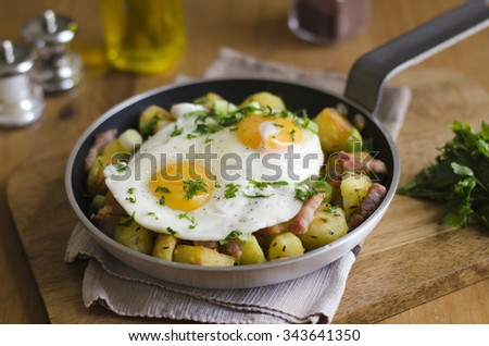 Fried eggs with roasted potatoes and bacon lardons - stock photo