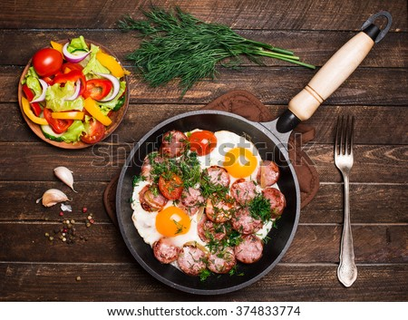 Fried eggs with sausage and tomatoes in frying pan served with salad on dark rustic background. Top view. - stock photo