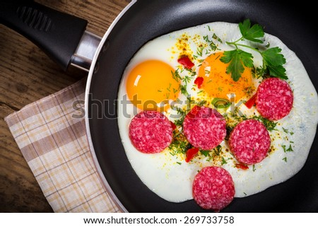 fried eggs with sausage in pan served on wooden table - stock photo