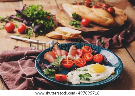 fried eggs with tomato, basil and prosciutto, table set for cozy breakfast at home